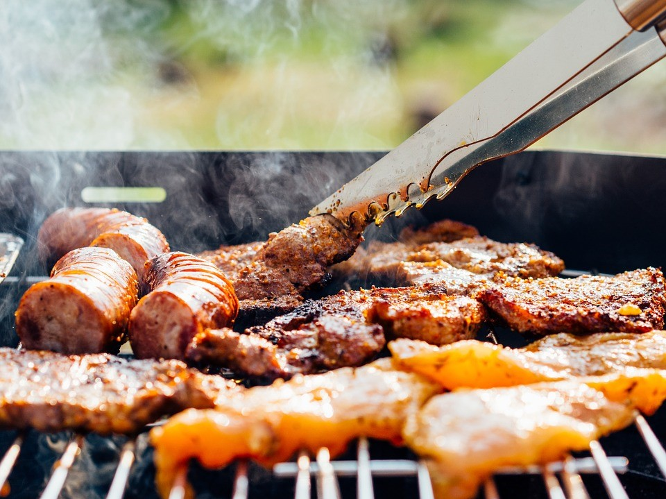 Food being grilled in a barbecue outside the kitchen
